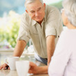 A handsome senior man enjoying coffee with his wife - Stock Photo