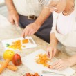 Older couple cutting vegetables together in the kitchen - Stock Photo