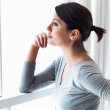 Woman by a window looking outside and expecting someone - Stockfoto