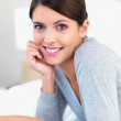 Closeup of a pretty female smiling in bed - Stock Photo