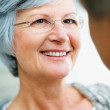 Closeup portrait of an elderly woman smiling at a man - Stock Photo