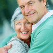 Portrait of a happy elderly couple hugging - Stock Photo