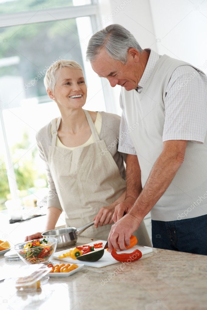 Happy senior man helping wife to cut vegetables at the kitchen — Stock Photo #3355185