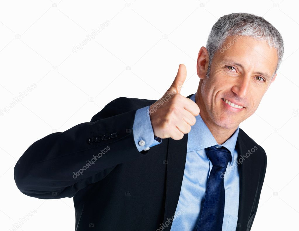 Portrait of a smiling and confident businessman giving approval by showing thumbs up gesture  Stock Photo #3358550