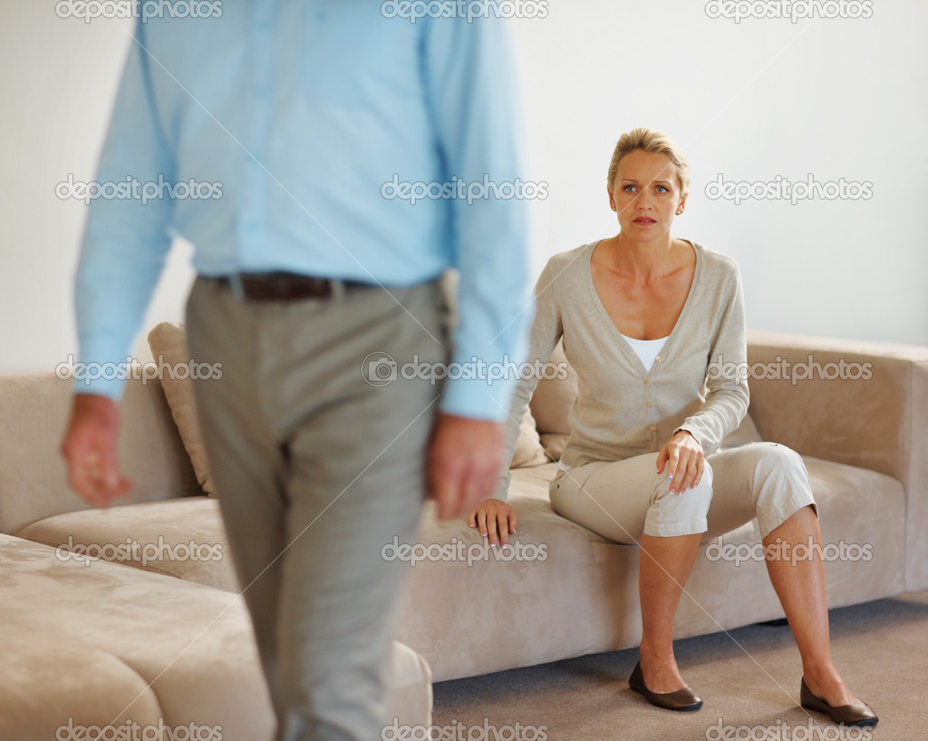 Relation issues - Middle aged woman sitting on couch at home with husband walking away on her — Stock Photo #3359347