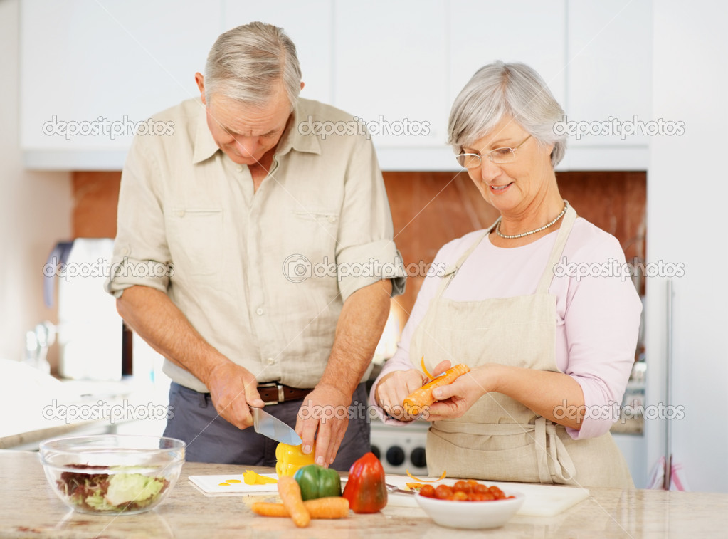 Elderly man helping his wife to cut vegetables in the kitchen — Foto Stock #3359431