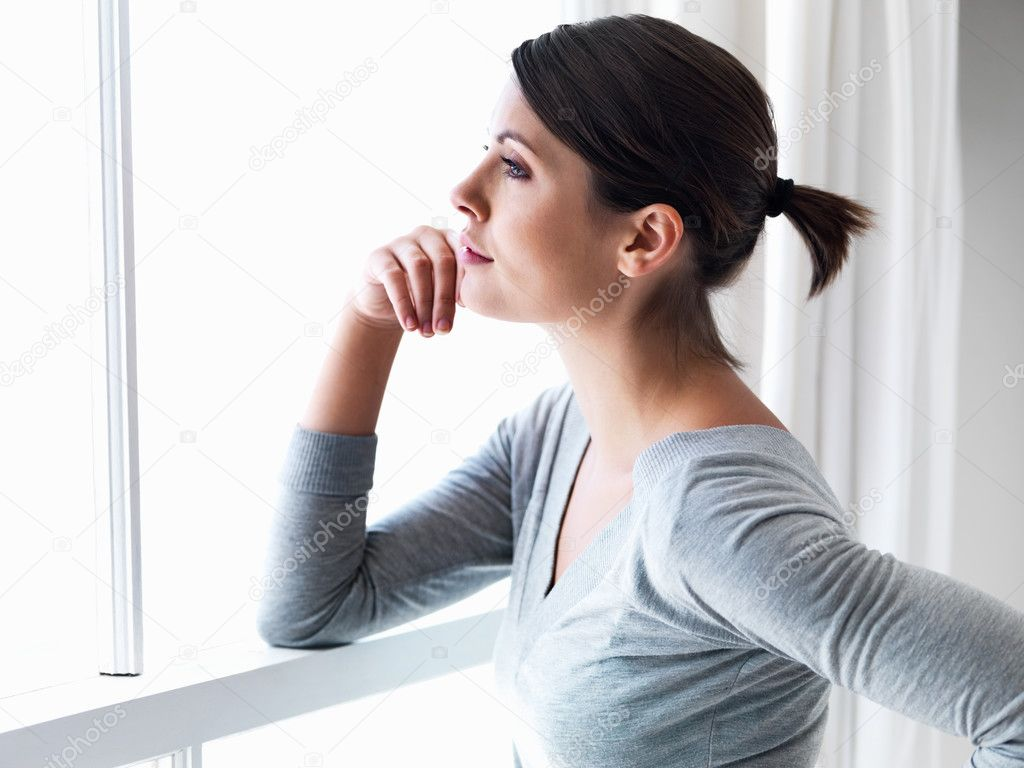 Young pretty female standing by a window looking outside expecting someone — Stock Photo #3359801