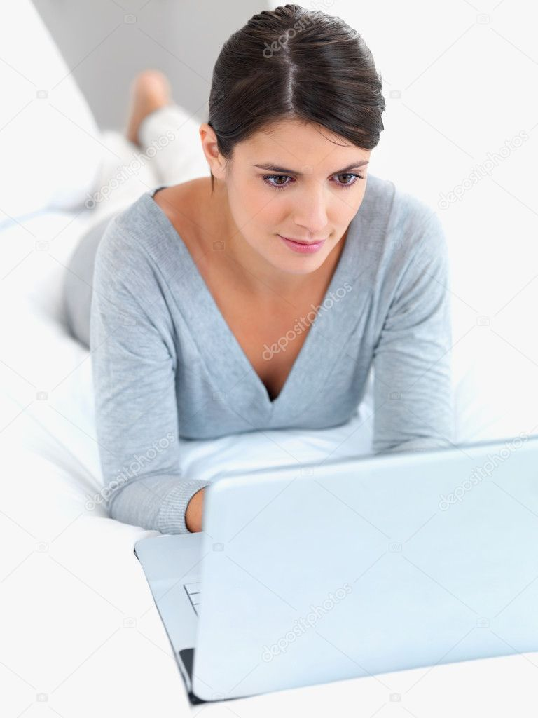 Pretty young woman lying relaxed on the bed working on a laptop  Stock Photo #3359826