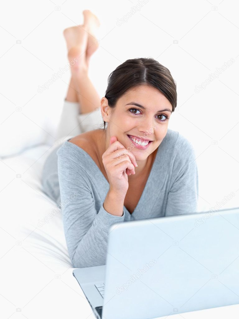 Portrait of a cute woman working on a laptop while lying relaxed in bed — Stock Photo #3359829