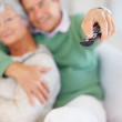 Royalty-Free Stock Photo: Retired couple sitting on the couch watching TV