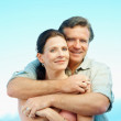 Romantic mature couple embracing against blue sky - Stock Photo