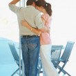Rear view of a romantic and serene couple by the porch - Stock Photo
