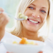 Beautiful mature woman eating a healthy bowl of cut fruits - Stock Photo