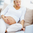 Pregnant woman searching information about childcare on internet - Stock Photo