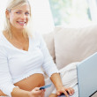 Mature pregnant female relaxing on a sofa with a credit card - Stock Photo