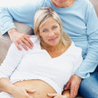 Royalty-Free Stock Photo: Happy mature pregnant woman with her husband relaxing on couch