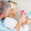 Couple deciding whether the wall should be pink or blue - Stock Photo