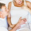 Top view of a pregnant couple in bed , man holding wife's tummy - Stock Photo