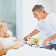 Husband serving breakfast to pregnant woman at the bed - Стоковая фотография
