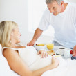 Loving man bringing breakfast o a pregnant woman&#039;s bed - Stock Photo