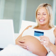 Happy pregnant woman using a credit card for online shopping - Stock Photo