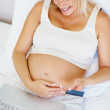 Relaxed pregnant woman using a credit card to shop online - Stock Photo