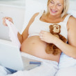 Happy pregnant woman buying baby products online - Stock Photo
