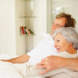 Senior couple spending a cozy time together in bed by copyspace - Stockfoto