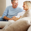 Affectionate mature man touching his pregnant wife's belly - Stock Photo