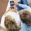 Top view of a couple looking at their unborn child's sonogram - Stock Photo