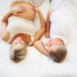 Happy mature pregnant woman with her husband lying on bed - Stock Photo