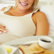 Breakfast being served to a mature pregnant woman on bed - Stock Photo