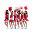 Smiling young cheerleaders posing against white - Stockfoto