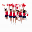 Squad of female cheerleaders jumping in the air on white - Foto Stock