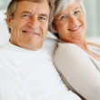 Romantic senior couple sitting together and smiling - Foto Stock