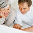 Royalty-Free Stock Photo: Elderly couple browsing the internet while in bed