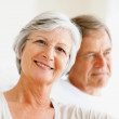 Closeup portrait of a smiling elderly couple sitting together - Stock Photo