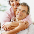 Smiling senior woman with arms around a man - Stock Photo