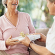 Senior woman recieving gift  from a man on their anniversary - Stock Photo