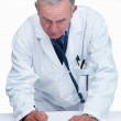 Senior successful doctor filling a report at a table on white - Stock Photo