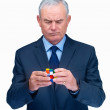 Senior business man trying to solve a  cube - Stock Photo