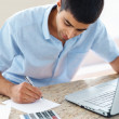 Young guy  with laptop doing monthly calculations - Foto de Stock