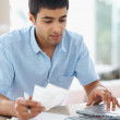 Young man paying bills using laptop at home - Stock Photo