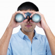 Young guy looking into binocular on an isolated background - Stock Photo