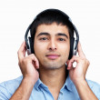 Royalty-Free Stock Photo: Young man listening to music on headphones against white
