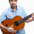 Smiling young guy playing a guitar isolated against white - Stock Photo