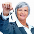 Real estate agent with keys on white background - Stock Photo