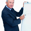 Senior business man giving a presentation using a flipchart - Stock Photo