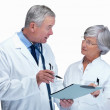 Doctor and nurse discussing a report on white background - Stock Photo