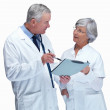 Doctor and nurse discussing over a report against white - Stock Photo